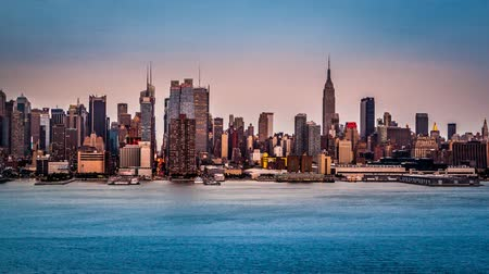 gün : Sunset and with a Supermoon rising behind the midtown Manhattan skyline Stok Video