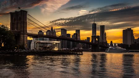 pomost : New York timelapse with Brooklyn Bridge going through sunset, twilight and night, while boats sail the East River.