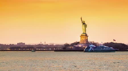 статуя : Timelapse with the Statue of Liberty in transition from sunset to night observed from Brooklyn New York City. Boats crisscross the Hudson River.