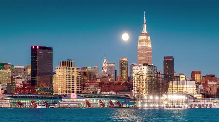 kereszt : Sunset, dusk and night with a Super Moon rising above New York skyline on November 14, 2016. On that night, the super-moon was the the biggest since 1948. Boats criss-cross Hudson River.