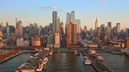 folga : Aerial drone footage of New York skyline. The camera takes off from Hudson River and lifts up, towards the 42nd street canyon.