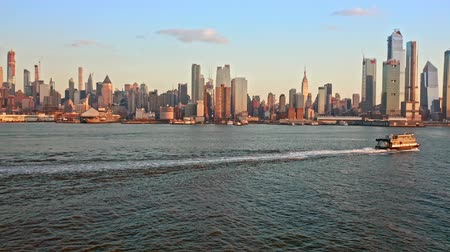 üzerinde : Aerial drone footage of New York skyline. The camera flies over Hudson River towards midtown Manhattan, while a boat crosses the frame. Stok Video