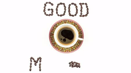 Stop motion animation with a top viewed cup of coffee and coffee beans, on a white background. Animated coffee beans form the words Good Morning.