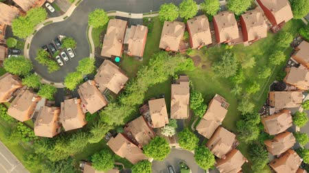 пригород : Late afternoon, birds eye view drone footage of a suburban community in New Jersey. Row of houses align along winding roads