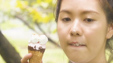 vacations cones : Young woman eating ice cream in garden park outdoors in summer sunshine in slow motion