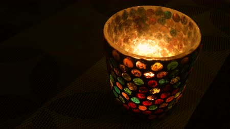 titular : Candle burns in a multicolored glass candlestick. Colorful flicker. Close-up.