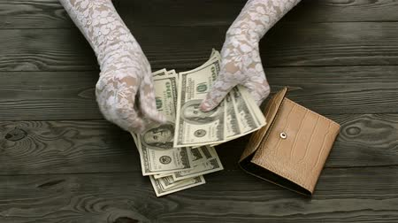 us banknotes : Womans hands, in white lace gloves, count the US dollars banknotes from black leather purse over a dark wooden background. Savings concept. Stock Footage