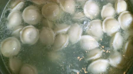 pelmeni : Process of cooking homemade dumplings. Meat dumplings in boiling water in a pan. Dumplings is traditional russian food. Food background. Close-up.