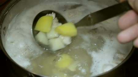 seethe : Cooking boiling broth for soup. Foam swimming on the top of boiling chicken meat and potatoes. Mixing a scoop.