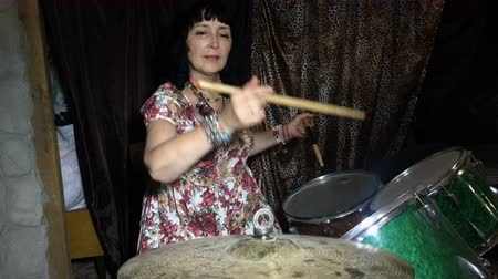 dobos : Adult woman has fun, learns to play on an old vintage drum set in a garage or basement.
