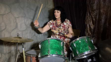 ритм : Adult woman has fun, learns to play on an old vintage drum set in a garage or basement.