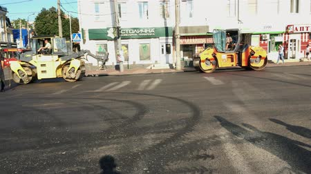 paving : Khmelnitsky, Ukraine, August 2018: - Road Construction. Asphalt paver rolls out of asphalt during the repair of the road in the city center.
