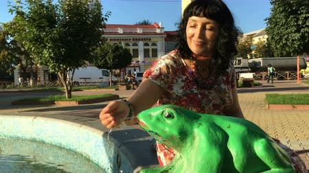 žába : Khmelnitsky, Ukraine, August 2018: - Adult stylishly dressed happy woman playing with a stream of water in a fountain. Fountain in the form of a frog. A summer sunny day. Downtown. Dostupné videozáznamy