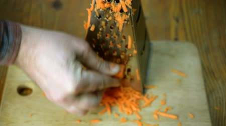 grating : Human hands cut carrots using a metal kitchen board. Stock Footage