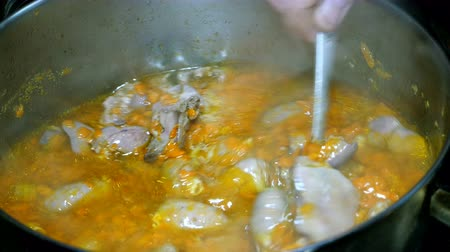 chicken recipes : Cooking homemade food. Goulash or thick soup of chicken giblets with carrots boils in a saucepan. It is stirred with a metal spoon. Stock Footage