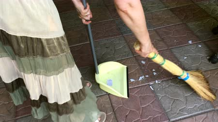 süpürge : Household chores. Woman sweeping splinters with a broom on a tiled floor outdoors.