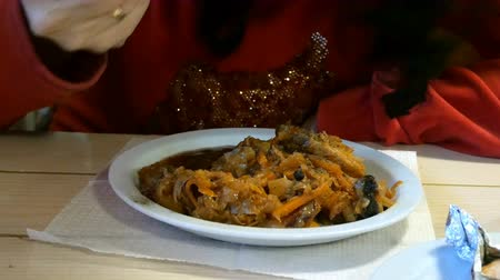 crauti : Cabbage stew or bigus with meat, in a restaurant or cafe. With the help of a fork. Fragment with hands.