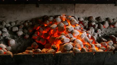 brilhantemente : Brightly burning hot briquettes in a brazier. Hot fire flames in a barbecue with red flames.