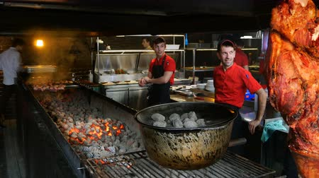 shish : Lviv, Ukraine, January 2018: - Cooking kebabs or barbecue in restaurant or cafe over charcoal. Workers on kitchen preparing barbecue with delicious grilled meat on skewers.