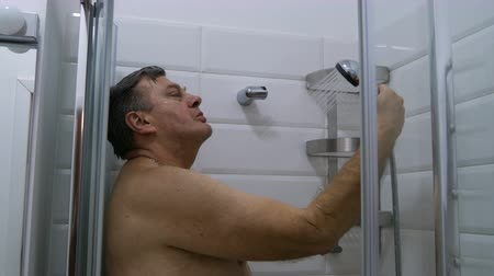 fikstür : Bathroom interior. Adult, caucasian, ethnic man, takes a shower with a shower head. Modern shower splashing water in the bathroom.