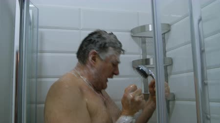 раковина : Bathroom interior. Adult, caucasian ethnicity man takes a shower. Modern shower splashing water in the bathroom.