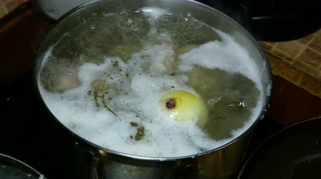 faca : Concept of home cooking. Do it yourself. Whole onion is thrown into boiling broth with foam. Vídeos