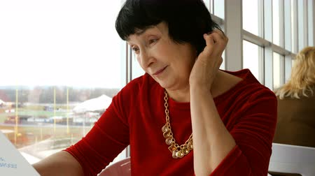 голова и плечи : Elegant aged woman, caucasian ethnicity, reads menu in restaurant or cafe, sitting by the big window.