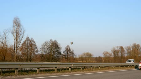 mode : Multi-lane highway with cars In the background, a balloon hangs over the trees. Stock Footage