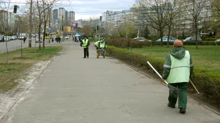 vassoura : Kiev, Ukraine, April 2019: - Janitors clean the sidewalks on the street in the city.