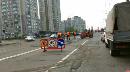 cloture : Kiev, Ukraine, April 2019: - Road workers are repairing the road at an intersection. Workplace is fenced off by signs.