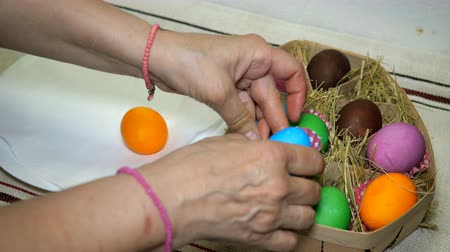 multi colorido : Homemade preparation for the holiday Easter. Easter eggs in basket with hay.