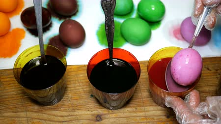 dyes : Homemade preparation for the holiday Easter. Easter eggs in different colors, dipping them into cups with multicolored dyes. Stock Footage