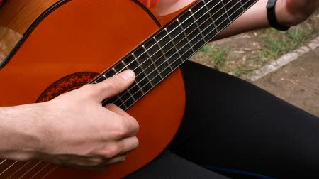 akord : Performance musician. Acoustic wooden guitar. Outdoors Close-up.