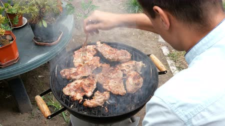 candida : Grilled food. Meat steak. Man turn over large meat meat steaks, grill on a metal grate. Weekend relaxation concept.
