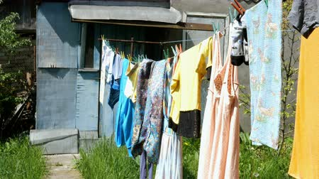 prendedor de roupa : Home work. Washed casual clothes and underwear, hanging on the floor in a village. Stock Footage