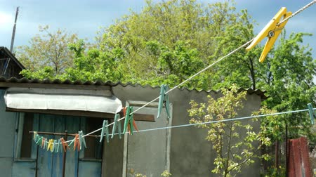 зажим : Household. Multicolored plastic clothespins, hanging on the clothesline