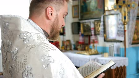 křest : Kiev, Ukraine, May 2019: - Young priest reads a prayer from the Bible.