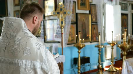 batismo : Kiev, Ukraine, May 2019: - Young priest reads a prayer from the Bible.