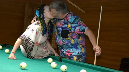 hure : Elderly family. Relax in billiard room. Huggings, kisses, rejoice and beat balls with cue. Selective focus.