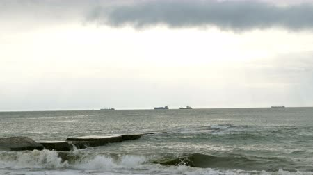 dalgakıran : Surf at Black Sea. Small waves splits with breakwater at Black sea near Odessa. Ships on the horizon. Coastline, splashing, crashing, seafoam.