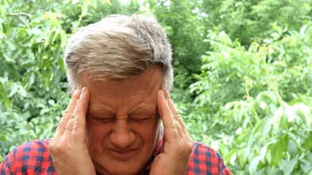 temporal : Portrait of caucasian ethnicity mature adult man having headache. Terrible migraine, pressure or health problems. He squeezes his head with his hands.