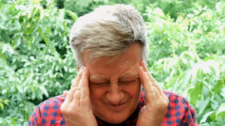 dor de cabeça : Portrait of caucasian ethnicity mature adult man having headache. Terrible migraine, pressure or health problems. He squeezes his head with his hands. He drinking a pill. Stock Footage