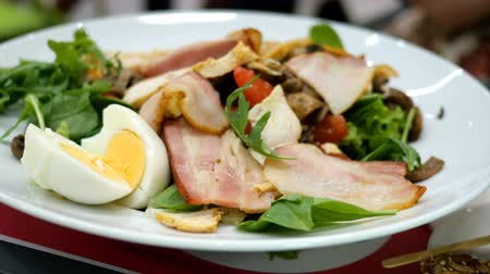 louça : Homemade cooking. Human hands decorate fresh salad with arugula, tomatoes, eggs and bacon in white plate. Close-up. Vídeos