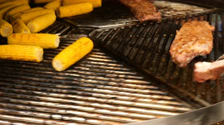 kukoricacső : Corn on the cob and pork steaks are roasted on a rotating grill or barbecue. Motion blur.