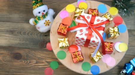 rotates : Decorative christmas or New Year gifts boxes collection rotates in circle on a wooden stand. Use for christmas desgn.