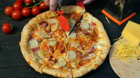 пепперони : Hands clumsily cut off pizza, on slices, with sausage, tomato and cheese, with special knife - cutter wheel . On wooden table there are also tomatoes and grated cheese.