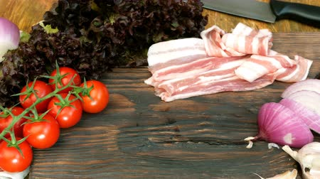 slanina : Homemade cooking. Products for delicious food. Sliced raw pork or beef brisket, vegetables: tomatoes, lettuce, onion, garlic, lie on a wooden kitchen board. In a rustic style.