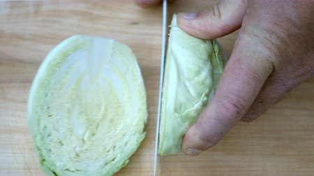 cortiça : Homemade cooking. Human hands cut cabbage head in half, with a sharp kitchen knife, on a wooden surface for cooking.