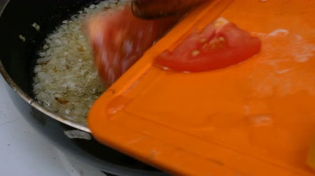 kaynatmak : Homemade kitchen. Sliced tomatoes and sweet peppers are thrown into a pan in which finely chopped onions are fried.