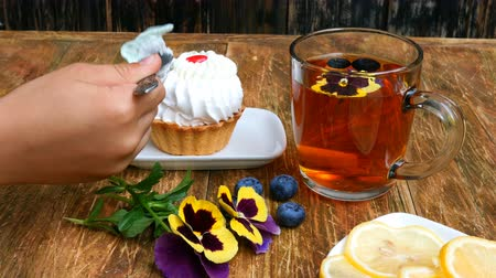 maceška : Child hand takes with teaspoon tasty fresh cake on saucer, on wooden table. On table there is also cup with tea, pansy flowers and saucer with lemon. Dostupné videozáznamy